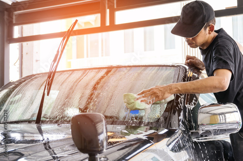 Car wash worker wearing a T-shirt and a black cap is using a sponge to clean the car in the car wash center, concept for car care industry.