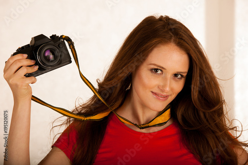 Fototapeta attractive beautiful woman holding a retro camera