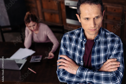 selective focus of pensive man and upset woman in kitchen at home, financial problems concept