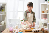 Boy cooking at home, making dough, buns and cookies - 195126016