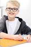 Nauka pisania. Uśmiechnięty chłopiec ćwiczy pisanie literek. - 195129073
