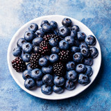 Blueberry and blackberry berries on a white plate on blue stone background. Top view. - 195140809