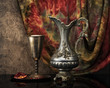 Retro still life with jug wine, metal goblet and a pomegranate