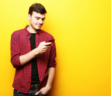 Happy young man talking on cell phone over yellow background