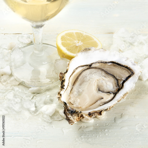 Closeup photo of an oyster with wine and lemon
