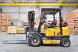 The forklift is old and scratched in a large and light warehouse. Yellow color - 195173808