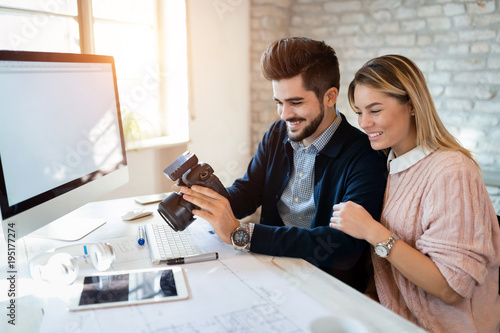 Picture of young attractive designers looking at camera