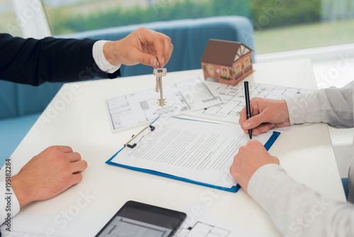 Conclusion of a contract for purchase of draft with realtor. Close-up photo of contract and draft.
