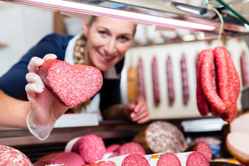 Sales woman in meat shop showing a heart shaped sausage to customer