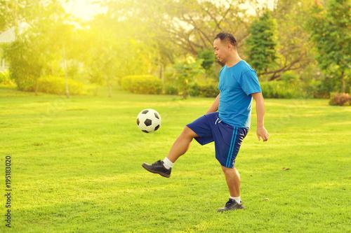 Aluminium Voetbal Asian man playing football alone in garden