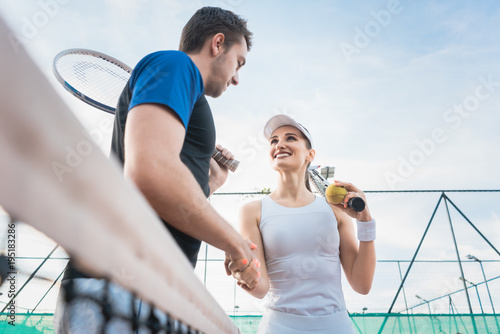 Fotobehang Tennis Tennis player man and woman giving handshake after match at the net