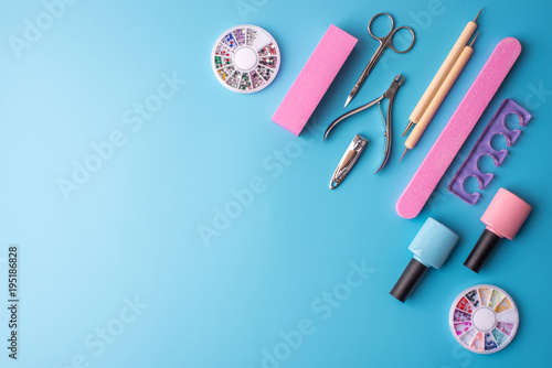 Aluminium Pedicure A set of cosmetic tools for manicure and pedicure on a blue background. Gel polishes, nail files and clippers, top view