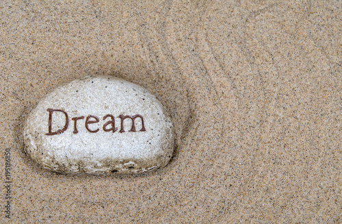 Plexiglas Zen Stenen close up of stone with dream sign in raked beach sand pattern