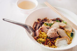 Thai egg noodle in white bowl with sliced red barbecue pork, pork ball, fish sausages close up on white background - 195187207