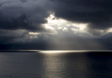 Sun Breaks Through Dark Clouds Over Ocean - 195190296