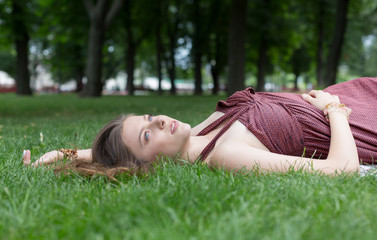 Beautiful young girl lying on grass in summer park
