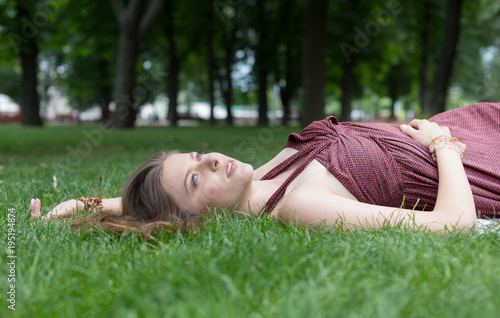 Fototapeta Beautiful young girl lying on grass in summer park