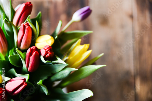 Spring background, postcard: bouquet of multicolored tulips on wooden background.