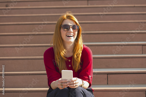 Attractive smiling woman using cellphone outdoors.
