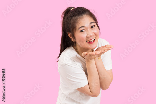 Cute asian woman blows kiss, hands on her chin, cute and happy, white shirt, pink background