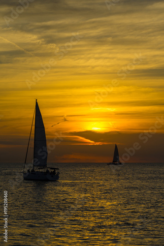 Keuken foto achterwand Oranje USA, Florida, Spectacular fire sunset and sailing ships on the ocean