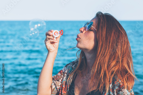 Young woman making water balloons at the seaside