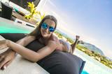 красивая молодая белая женщина лежит на надувном матрасе в бассейне на фоне моря в Таиланде