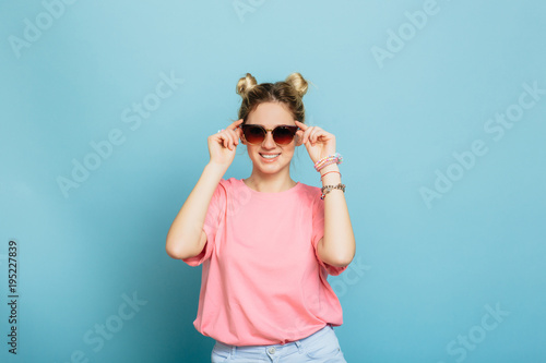pretty young woman wearing pink clothes adjusting her sunglasses and smiling, while standing against blue background. Looking just perfect.