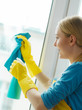 Girl cleaning window at home using detergent rag