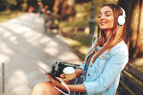 Attractive young women enjoying music and drinking coffee on a sunny day in the park