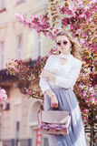 Outdoor portrait of young beautiful girl posing in street of european city, blooming trees on background. Model wearing stylish sunglasses, wrist watch, holding pink bag. Female fashion concept - 195247042