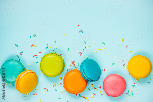 Aluminium Macarons Top view of colorful macaroons and sugar sprinkles arranged over blue background.