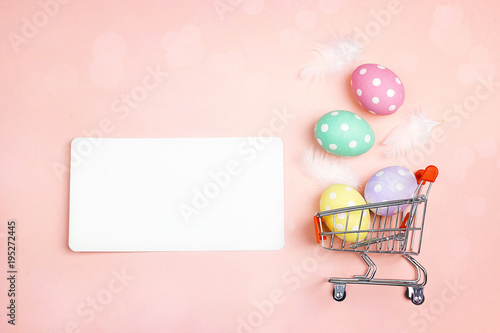 Shopping trolley with Easter eggs and copy space on pink background.