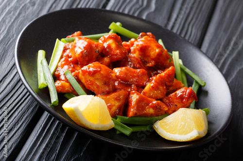 Spicy chicken pieces in red sauce with green onions and lemon close-up on a plate. horizontal