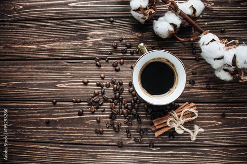 Tuinposter Koffiebonen close-up view of roasted coffee beans, cup of coffee, cotton flowers and cinnamon