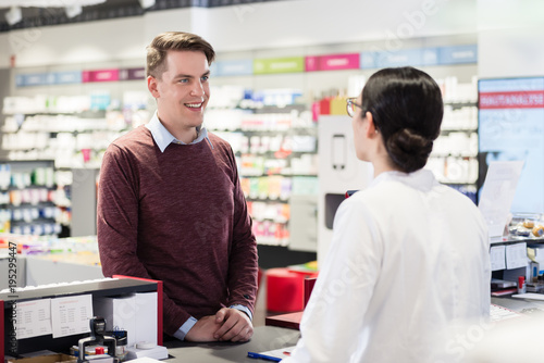 Deurstickers Apotheek Portrait of a handsome young man and happy customer listening to the recommendations and the advice of a reliable female pharmacist in a contemporary drugstore