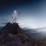 Portrait of astronaut in a space suit. Futuristic astronaut on the planet, standing on top of a mountain and stretches his hand away - 195297062