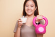 Healthy Asian woman drinking a glass of milk and kettlebell