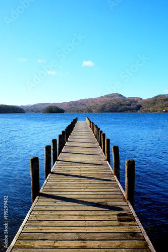 Plexiglas Pier very long beautiful wooden jetty, jutting out from the centre of the image into a calm blue lake with hills of forest and meadows in background