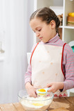 Girl cooking and having fun at home, breaking egg and making faces - 195301887