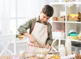 Boy cooking at home, making dough, buns and cookies - 195302003