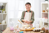 Boy cooking at home, making dough, buns and cookies - 195302018