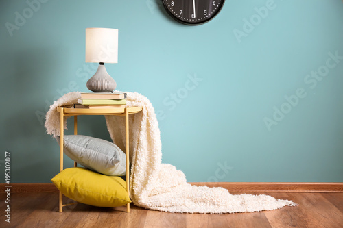 Elegant lamp and books on table in room interior near color wall