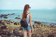 back view of young woman in sunglasses with backpack looking at ocean
