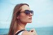 portrait of beautiful woman in sunglasses looking away