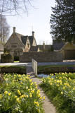 Cotswold cottage and the River Eye in spring sunshine, Lower Slaughter, Gloucestershire, UK - 195306444