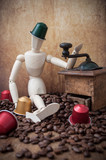 wooden puppet with coffee espresso capsules in arms on coffee beans - concept coffee addiction - 195306469