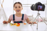 Love taste. Happy pre-teen girl posing for the camera and laughing cheerfully while eating gummies and recording it for her video blog