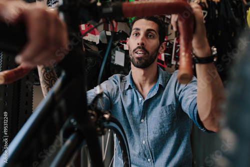 Worker inspecting a bicycle in workshop