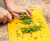 Dill cutting with a knife on the board - 195317881